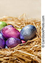 Chocolate Easter eggs in a natural straw nest