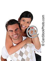 Couple holding an at symbol