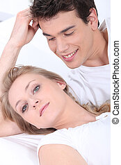 Young woman and young man laid on a couch