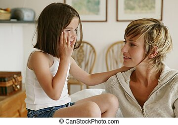 Little girl whispering secrets to her mom
