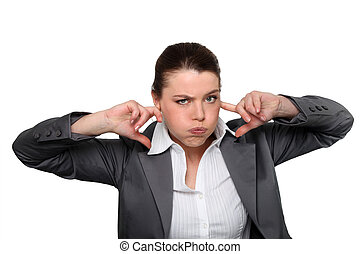 Brunette office worker with fingers in ears