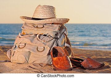 Vacation - Knapsack, wicker hat and sandal on the sandy...