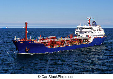 Oil Tanker - Oil tanker underway at sea over blue sky and...