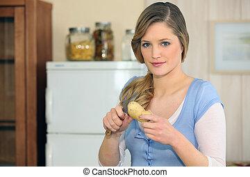 Woman cutting a potato