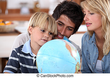 Young family looking at a globe