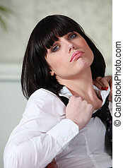Businesswoman pulling at her shirt collar