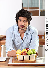 Man in kitchen leaning on countertop