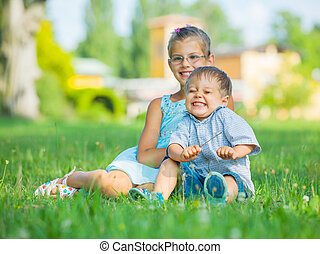 Little boy and his sister in the summer park