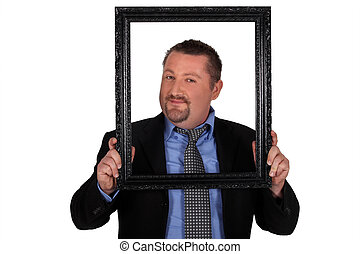 Businessman carrying frame in front of his face
