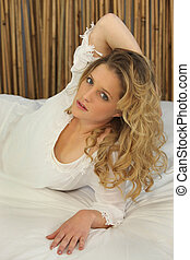 Woman with long blonde hair reclining on a bed