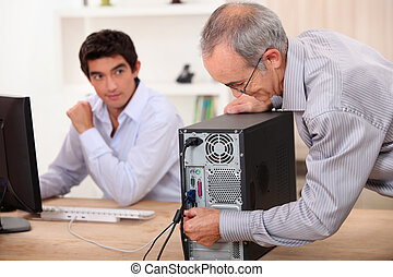 old man plugs a computer under the watch of a young man