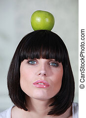a woman holding an apple on her head
