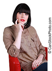 Woman sitting in a red chair contemplating the camera