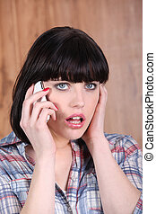 Shocked woman with mobile telephone