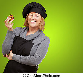 portrait of middle aged cook woman holding a delicious homemade muffin over green background
