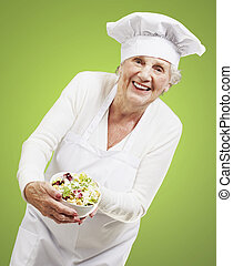 senior woman cook holding a bowl with salad against a green...