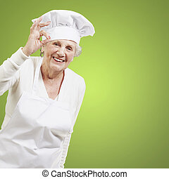 senior woman cook doing an excellent symbol against a green...