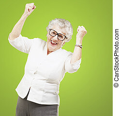 portrait of a cheerful senior woman gesturing victory over...