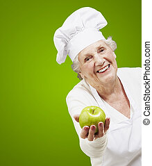 senior woman cook offering a green apple against a green...