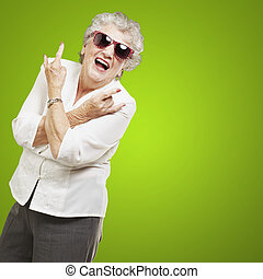 portrait of senior woman doing rock symbol over green...