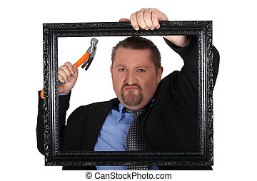 Businessman with a hammer and frame