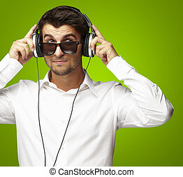 portrait of young man listening to music using headphones over green