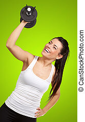 portrait of young girl training with weights over green...