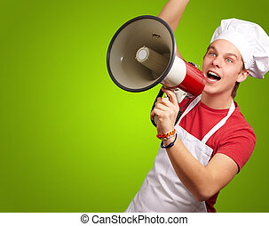 portrait of young cook man shouting with megaphone over green background
