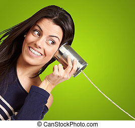 Young woman hearing using a metal tin can over green...
