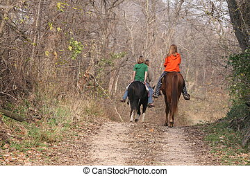 Equine riders on a dirt road