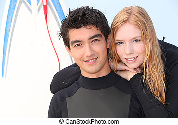 Two young surfers in wetsuits