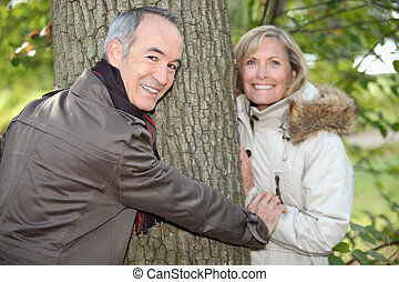 Older couple hugging a tree trunk in the autumn