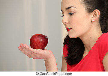 Woman holding a red apple in the palm of her hand