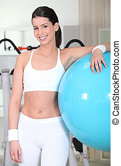 Young woman with a big blue exercise ball