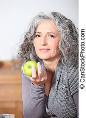 beautiful mature woman eating green apple
