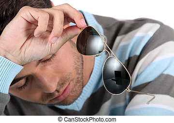 Tired man holding sunglasses