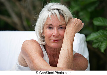 Grey-haired woman sat in garden