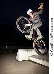 boy jumping with his bike over a ramp by night