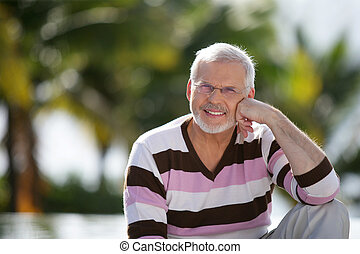 Grey-haired man sat in garden