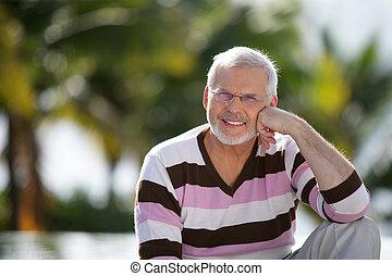 Grey-haired man sat in garden