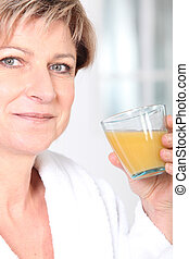Mature woman with a glass of orange juice