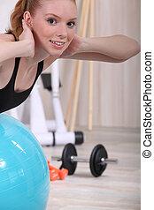 Woman balancing on gym ball