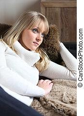 Dreamy woman lying on a sofa