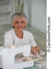 Elderly lady using sewing machine