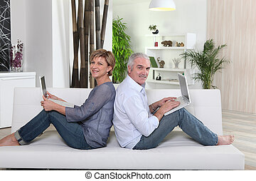 Couple each working on their own laptop