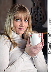 Young woman with a hot drink at home