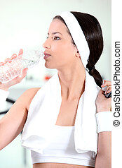 young woman drinking water after sport