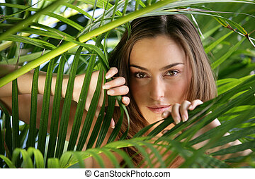 Woman peering through branches