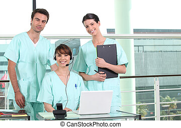 two nurses standing and a nurse using a headset
