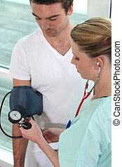 Young nurse taking blood pressure of a man